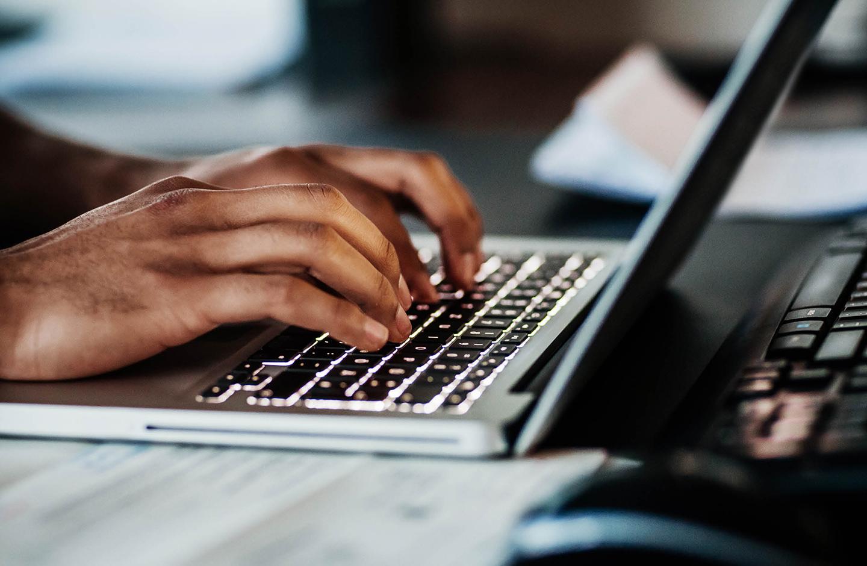 Nahaufnahme von zwei Händen, die auf der Tastatur eines Laptops tippen.