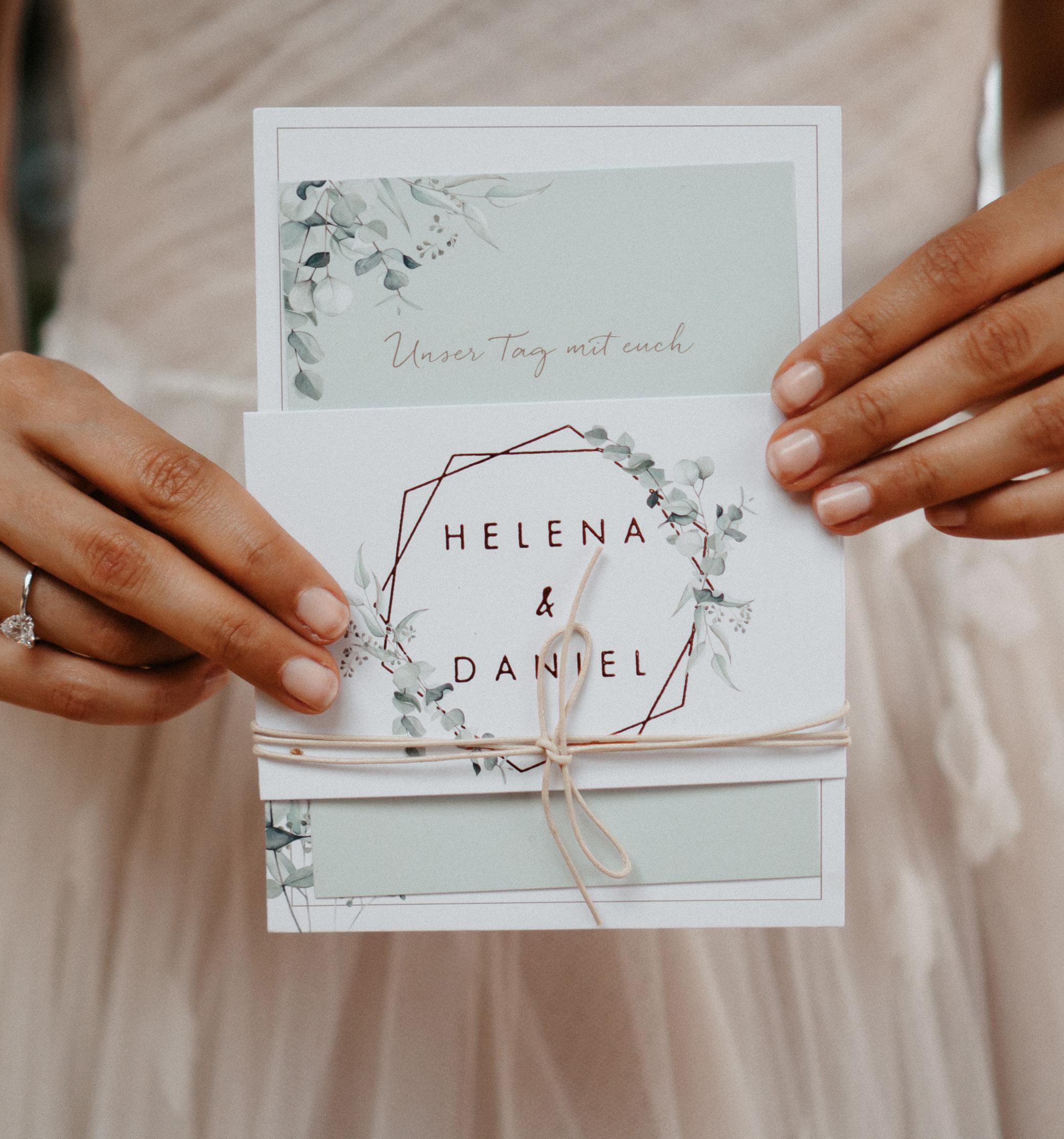 """Hochzeitseinladung """"Soft Greenery"""" als Kartenset mit Eukalyptus Zeichnung wird von der Braut gehalten."""