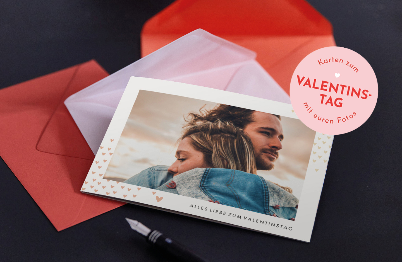 Valentinstag liegt auf orangem Umschlag. Auf der Karte ist ein verliebtes Pärchen und Herzchen.