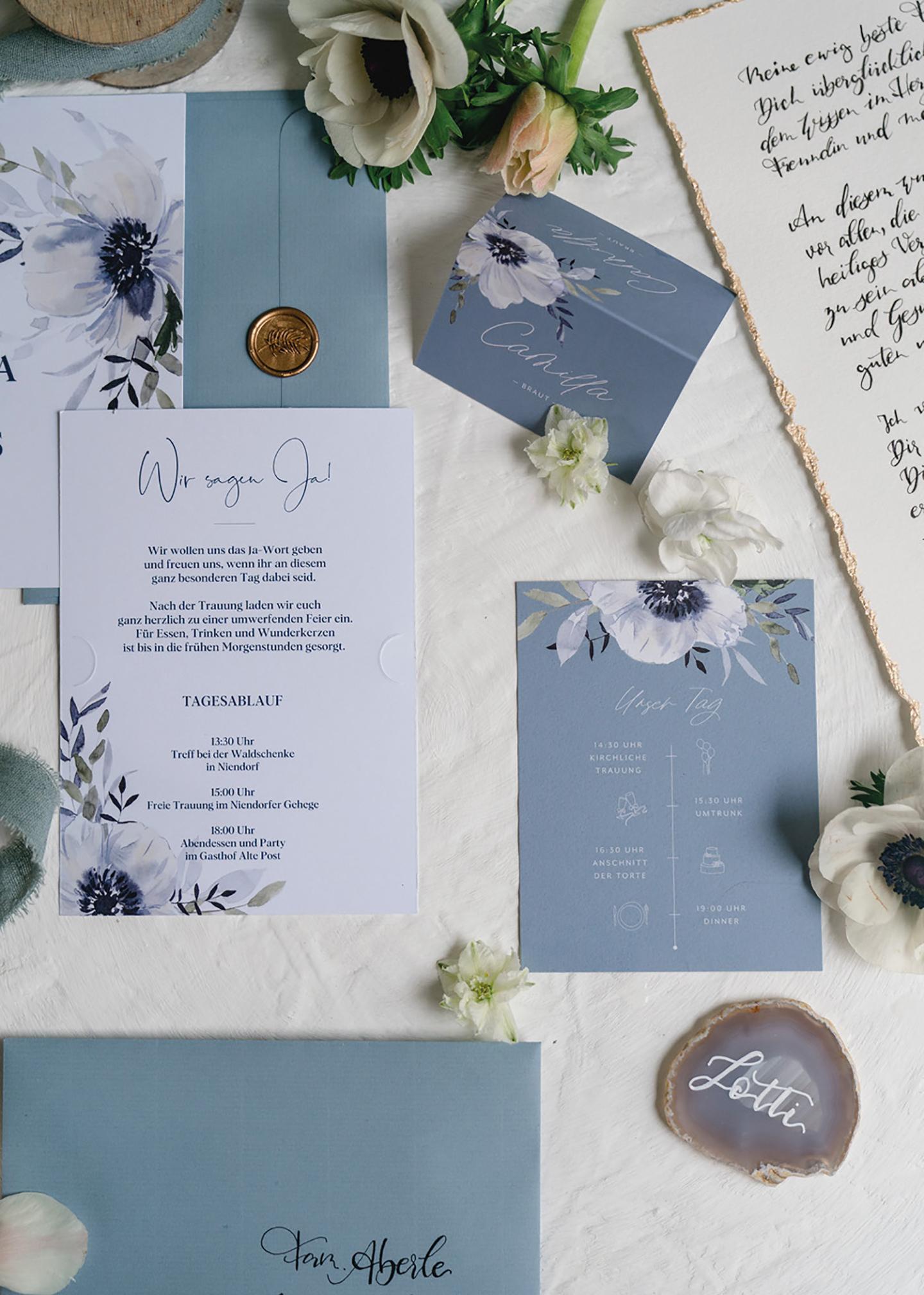 Die Hochzeitspapeterie des Paares wurde in hellblauen und weißen Tönen gestaltet. Auf der Papeterie findet sich eine detailtreu gezeichnete große Blüte in weiß und dunkelblau.