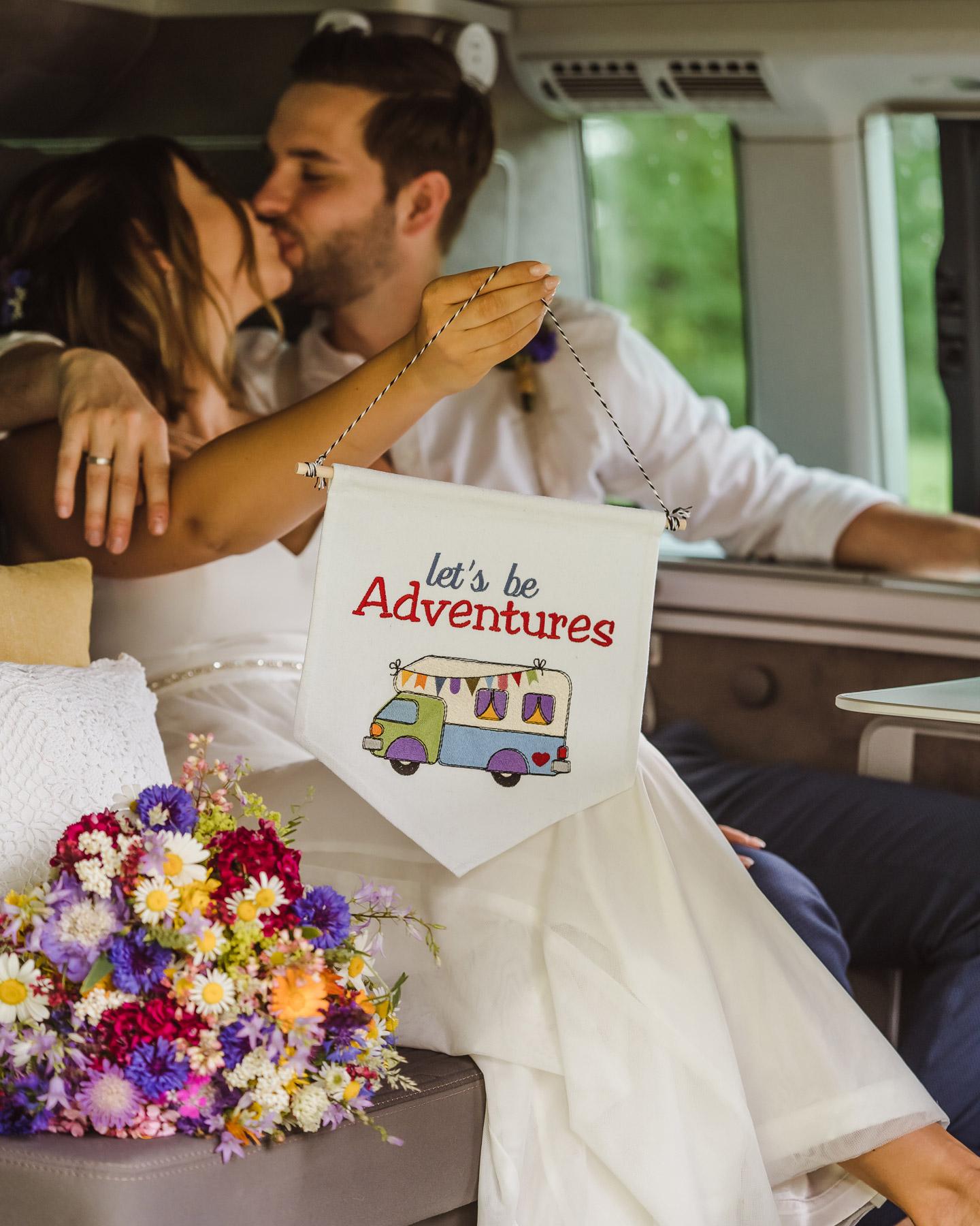 """Brautpaar hält """"Lets be adventures""""-Wimpel in die Kamera bei ihrer Camper Hochzeit."""