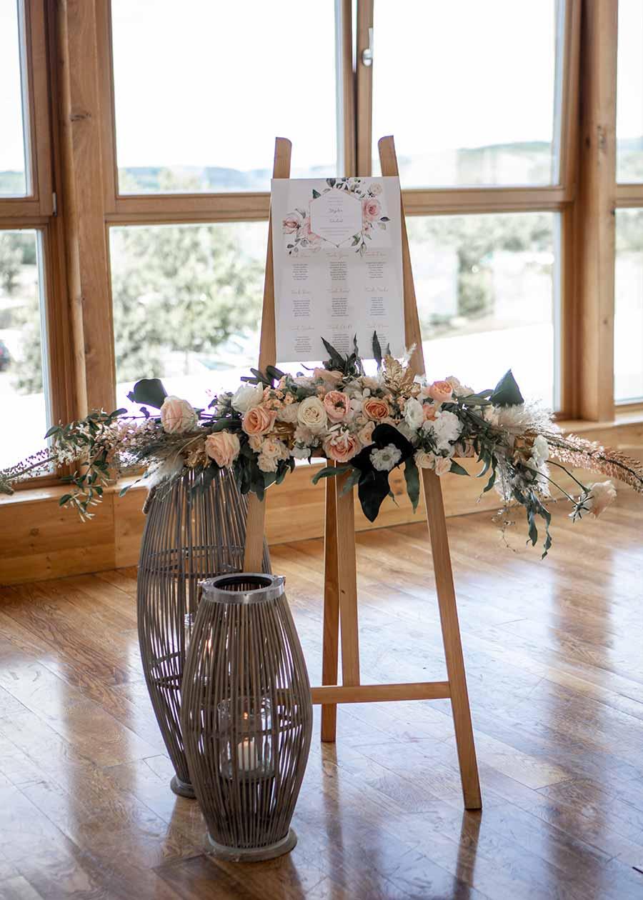 DIY Idee: Der Sitzplan steht auf einer Holzstaffelei und ist dekoriert mit einem Blumenbouquet.