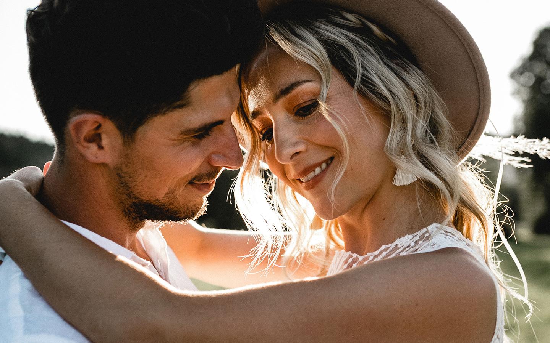 Verliebte Blicke tauschen Braut und Bräutigam im Sonnenlicht aus.