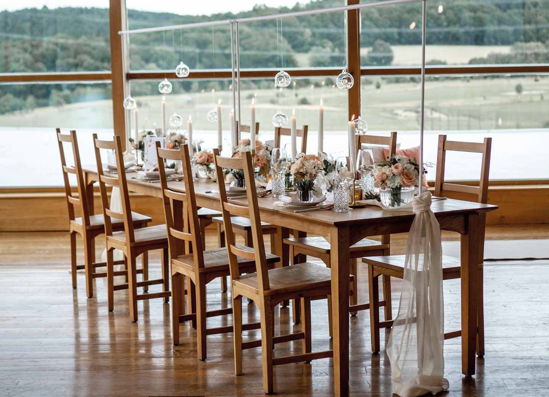 Hochzeitdeko Checkliste Tisch ist mit Kerzen Blumen und Sukkulenten dekoriert.