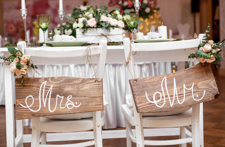 Tisch des Brautpaares. Die Stühle sind mit Mr. und Mrs. Schildern aus Holz geschmückt.