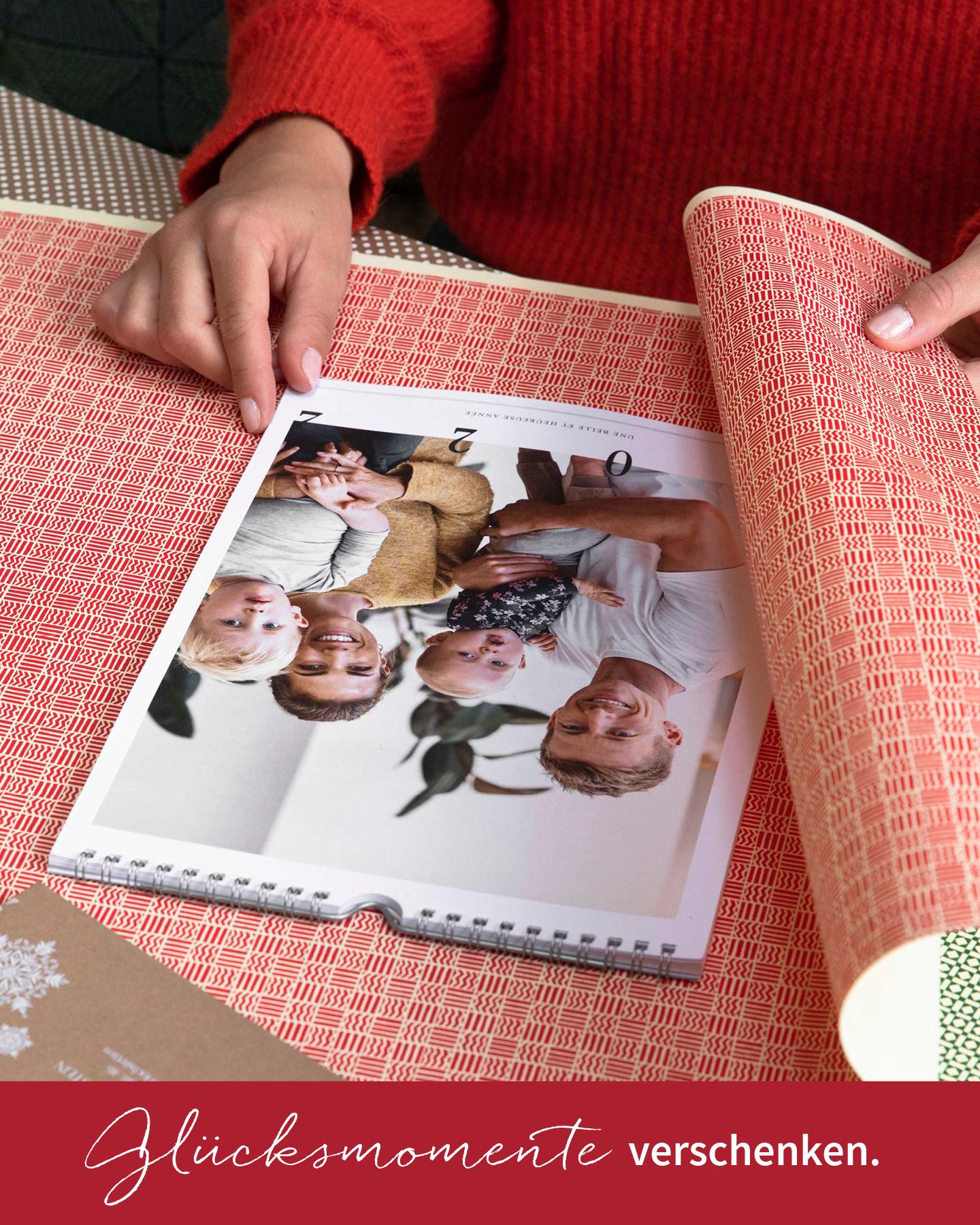 Fotokalender für die Wand wird mit bunten Geschenkpapier zu Weihnachten eingepackt.