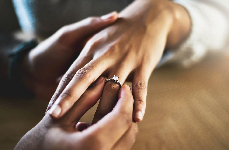 Detailaufnahme von zwei Händen, wie der Mann der Frau einen Ring and den Finger steckt.