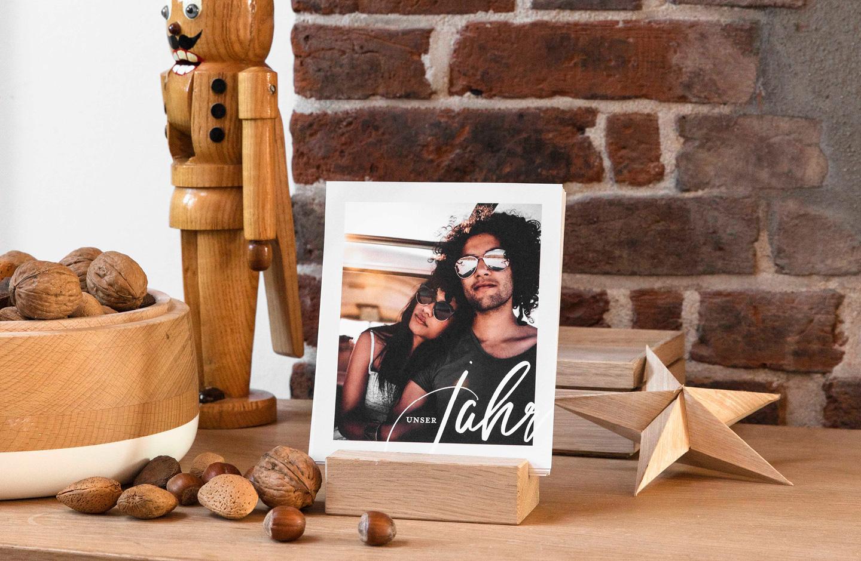 Fotokalender mit Foto von verliebten Pärchen steht auf einem Holztisch und ein Nussknacker steht daneben.