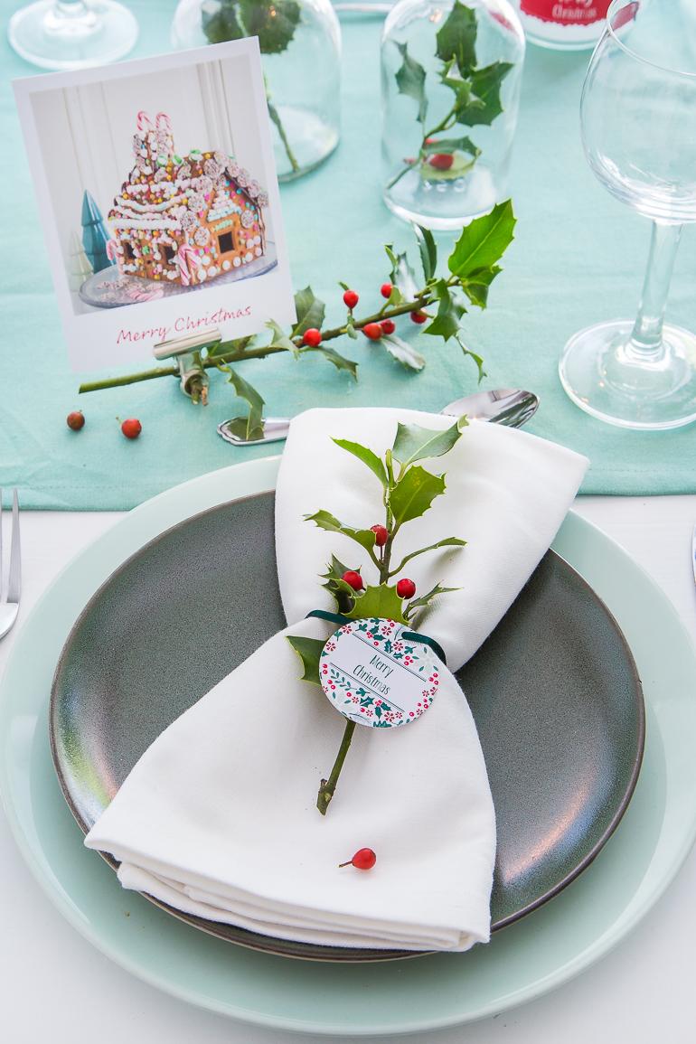 Serviette mit Ilex-zweig und Anhänger als Tischdekoration zu Weihnachten.