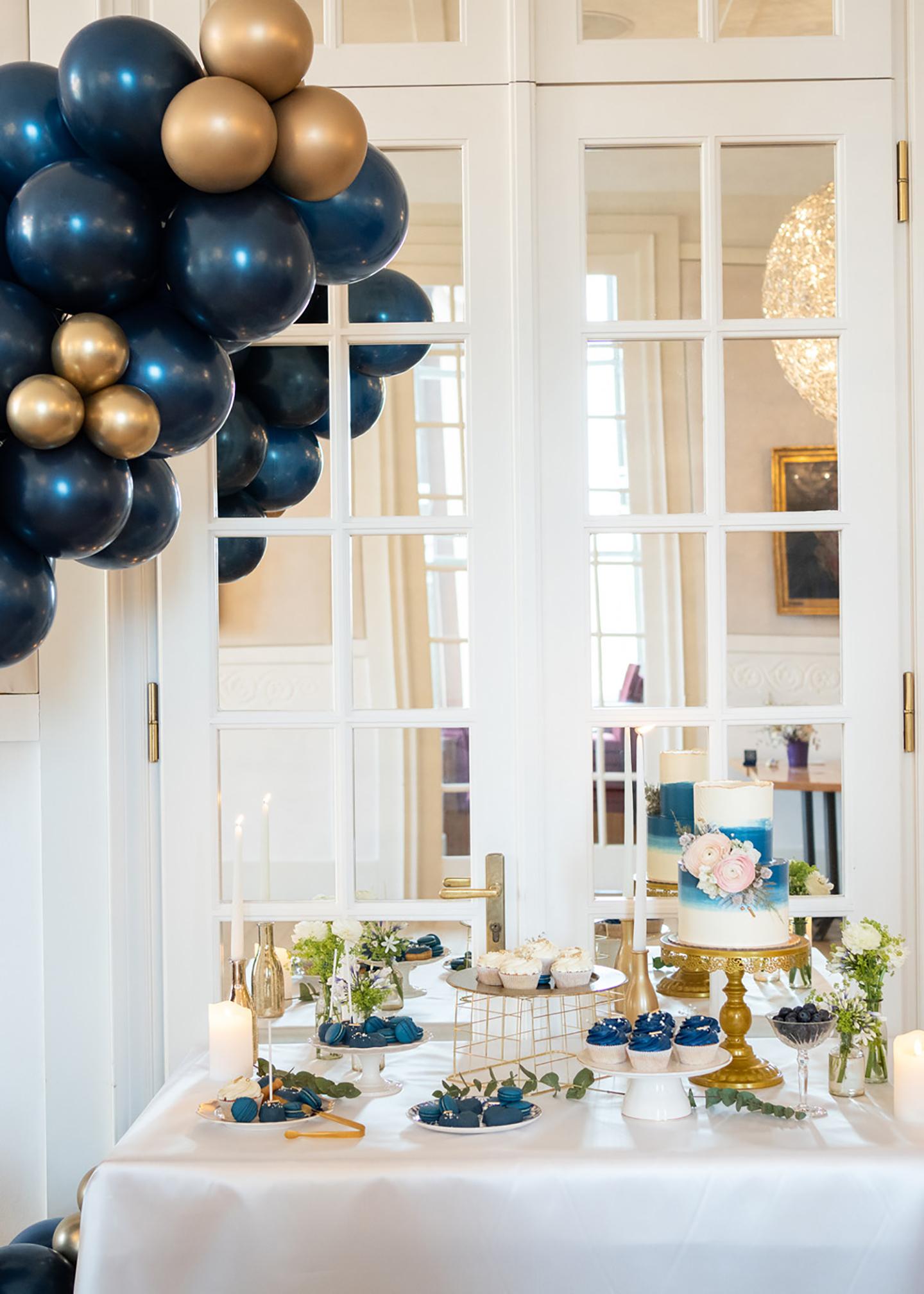 Die Hochzeitslocation von innen wurde dezent geschmückt, mit blauen Ballons und goldenen Elementen. Der Tisch, auf dem Ein Buffet aus der Hochzeitstorte und weiteren süßen Gebäckspeisen, besteht, ist auf einem extra Tisch angerichtet.