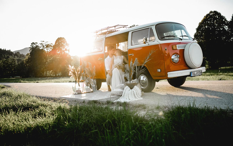 Der rote Bulli steht auf einem unbefahrenen Landweg neben einer grünen Wiese. Das Brautpaar sitzt im hinteren Bereich des Wagens und küsst sich. An der Tür des Bullis stehen Vasen mit Pampasgras zur Deko, sowie ein Teppich. Der Bulli ist weiß und rot.