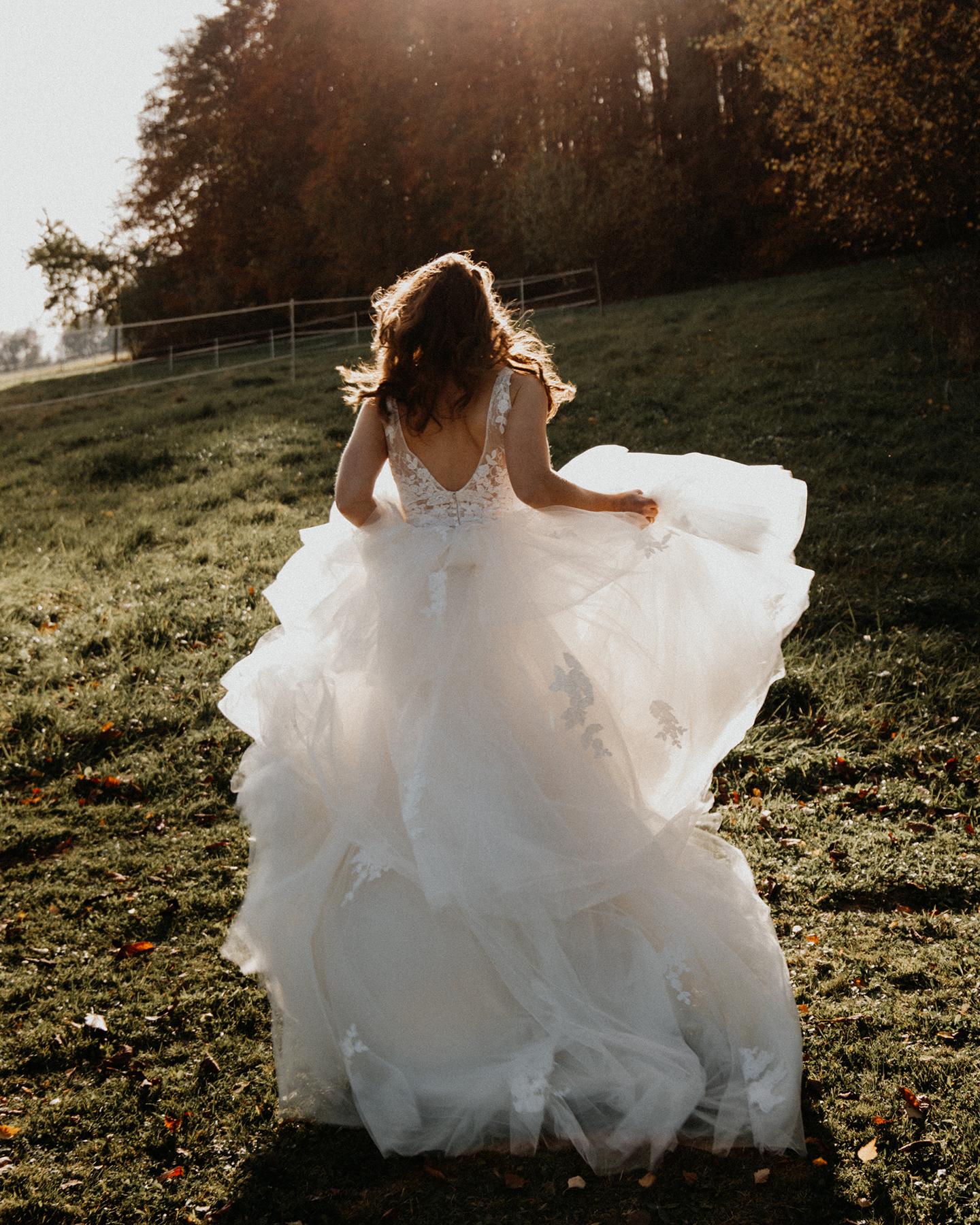 Boho Braut rennt glücklich mit wehendem Brautkleid über eine Wiese bei Sonnenuntergang ihrer Picknick Hochzeit.