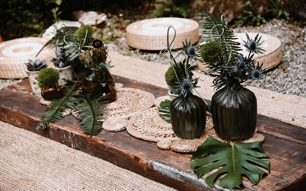 Grüne, stilvolle Vasen in moderner Form stehen liebevoll angeordnet auf geflochtenen Tischsets.