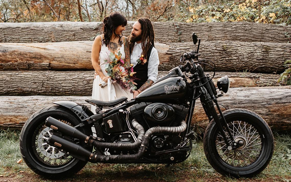 Frisch getrautes Pärchen vor Kulisse aus Baumstämmen in der Natur, im Hochzeitsoutfir mit Brautstrauß und Harley im Vordergrund.
