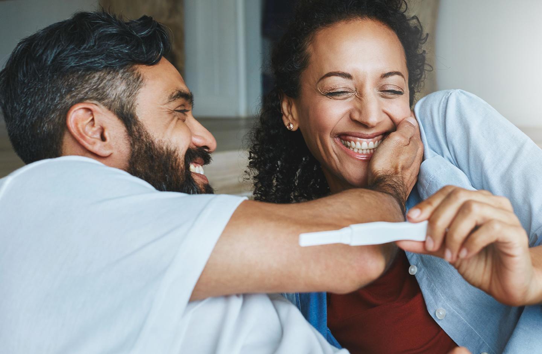Paar guckt glücklich auf den positiven Schwangerschaftstest