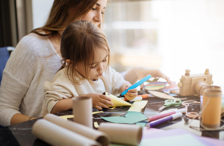 Nachhaltig Familie: Mama bastelt mit Tochter aus alten Klopapierrollen etwas Neues.