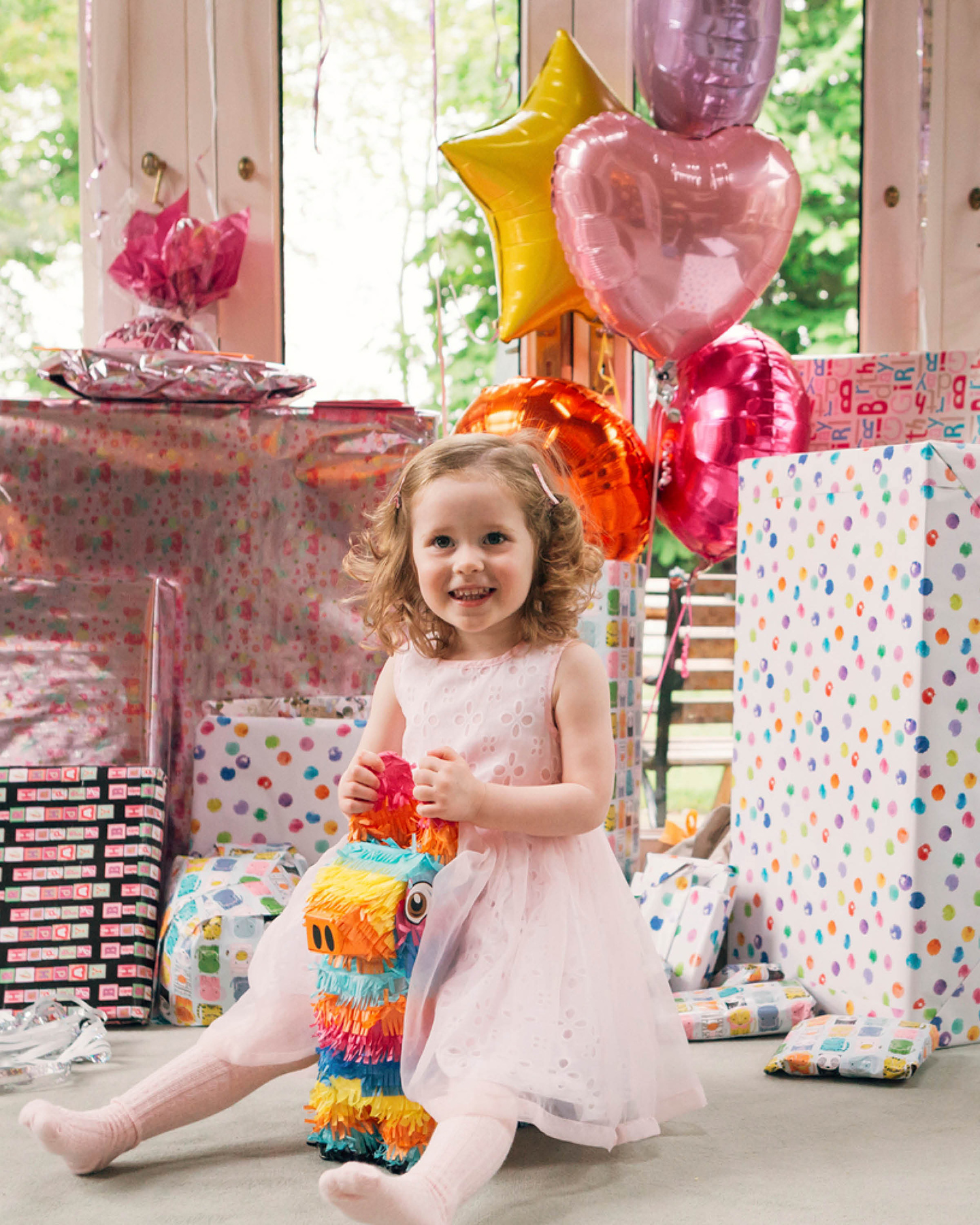 Mädchen in rosafarbenem Kleid sitzt vor einem großen Berg an Geburtstagsgeschenken. Helium gefüllte Luftballons in Herz- und Sternform zieren die Geschenke.