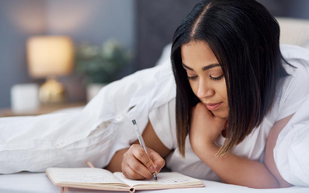 Frau schreibt in Schwangerschaftstagebuch