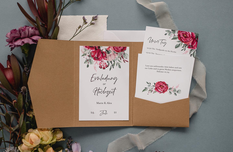 Hochzeitstrend 2021: Pocketfold Einladung aus Kraftpapier mit floralem Design liegt auf hellblauem Hintergrund.