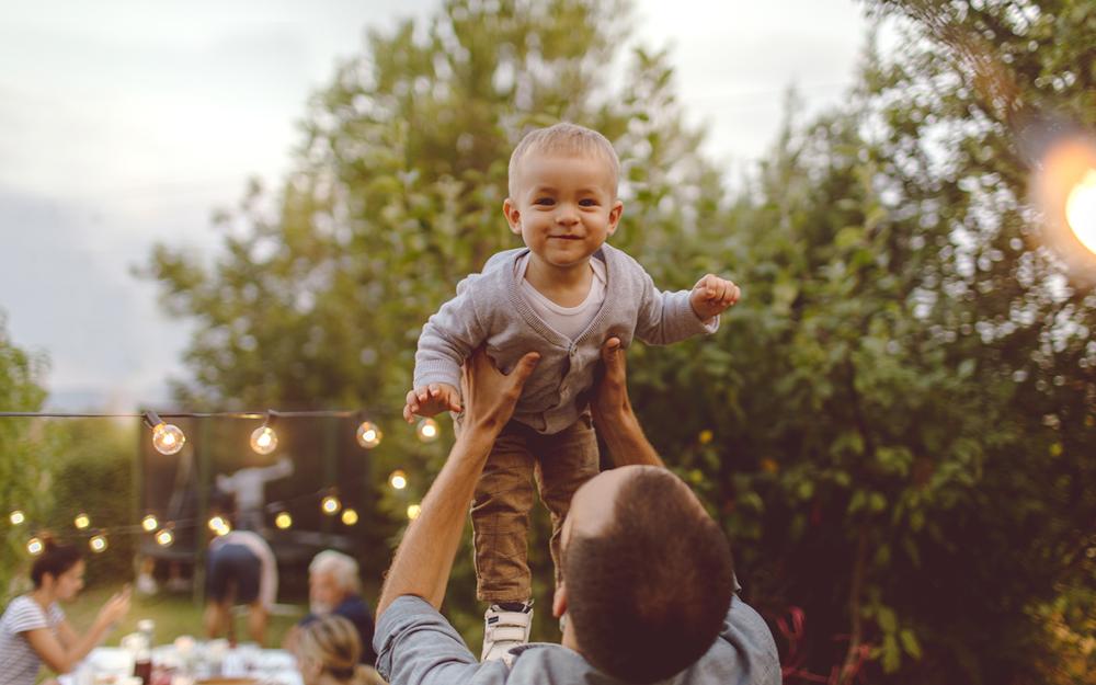 Vater hebt seinen Sohn bei Taufe im Garten hoch