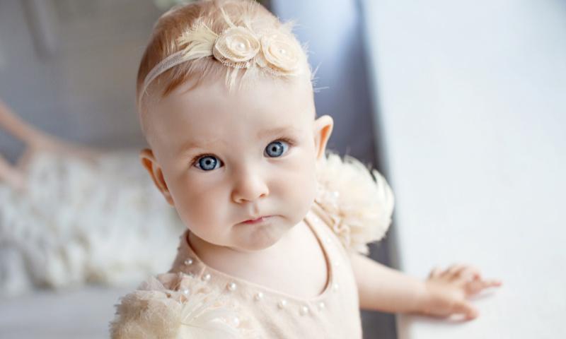 kleines Mädchen mit beige farbenen Taufkleid und Haarreif im Haar guckt in die Kamera