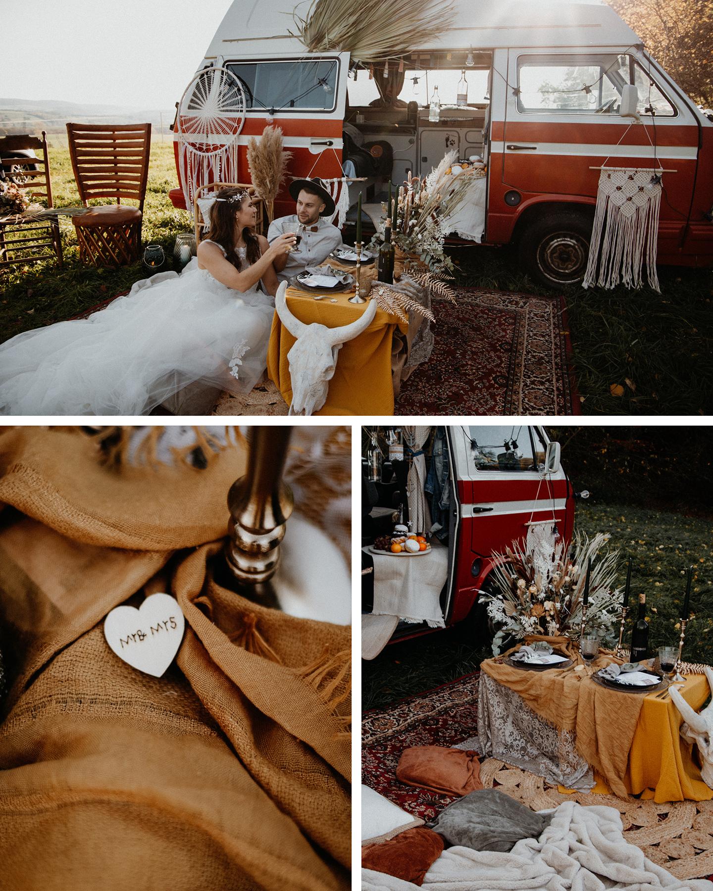 Brautpaar picknickt vor Hochzeitsbulli im Bohostil mit Traumfängern und Makramee-Elementen.