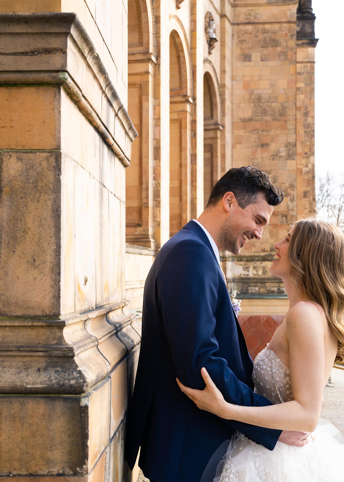 Das firsch vermählte Hochzeitspaar, bestehend aus Braut und Bräutigam schaut sich verliebt und glücklich lachend an und strahlt über das ganze Gesicht.