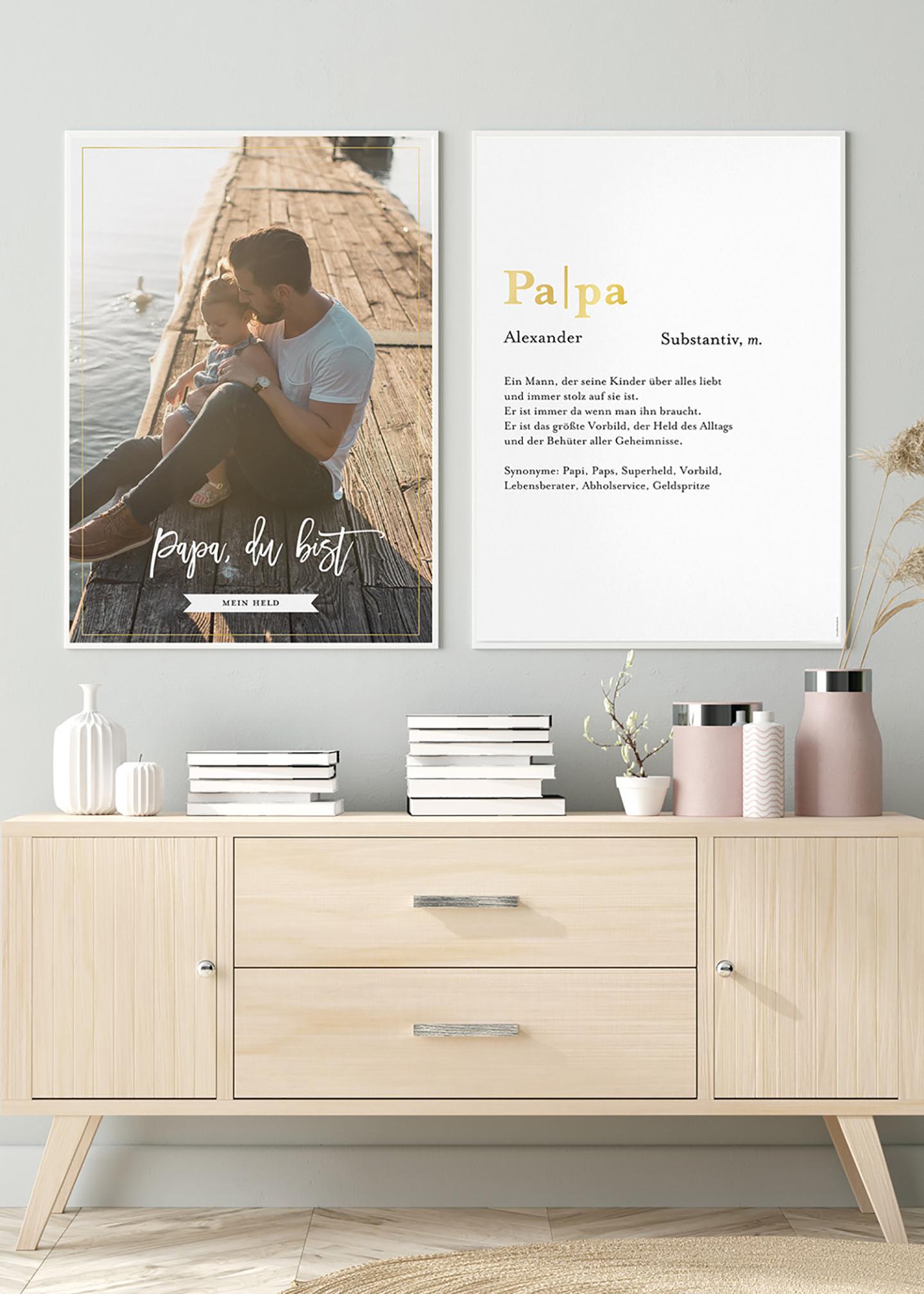 Zwei wunderschöne Poster mit Bild von Vater und Kind sowie einem Spruch hängen über einer Kommode an der Wand.