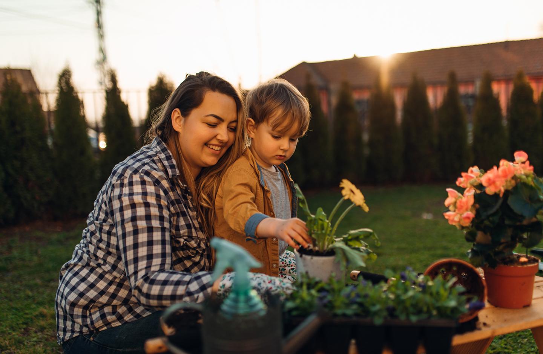Nachhaltig im Garten als Familie: Baby topft mit ihrem Kleinkind Blumen ein.