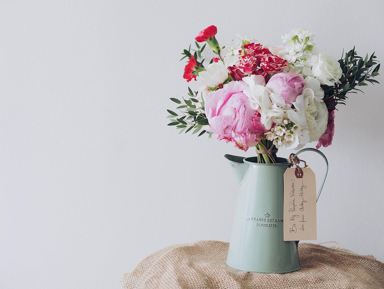 Blumenstrauß mit Pifngstrosen & weißen Rosen wird als Geschenk zum Valentinstag verschenkt.