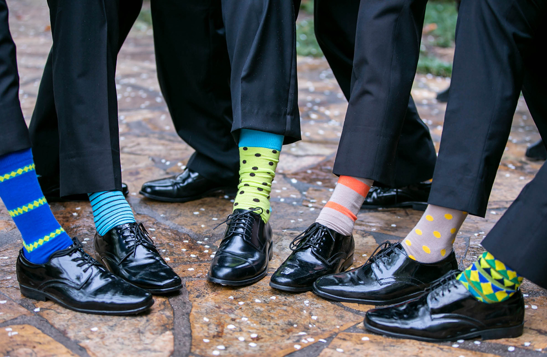 Männer mit Anzug ziehen gleichzeitig ihre Hosenbeine hoch, damit die verschiedenen bunten Socken, die sie tragen, sichtbar werden.