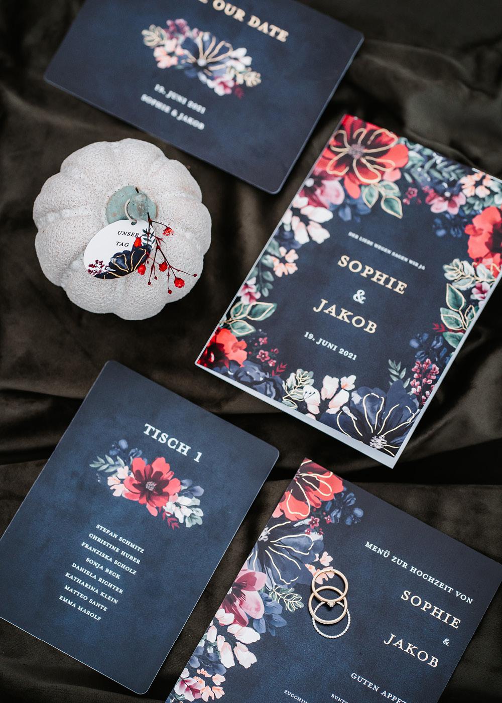 Papeterie, die durch ihre Farbe und Leuchtkraft hervorsticht: dunkelblaue Einladungskarte, Save the Date und Tischkarten mit bunten Blumen und goldener Veredelung.