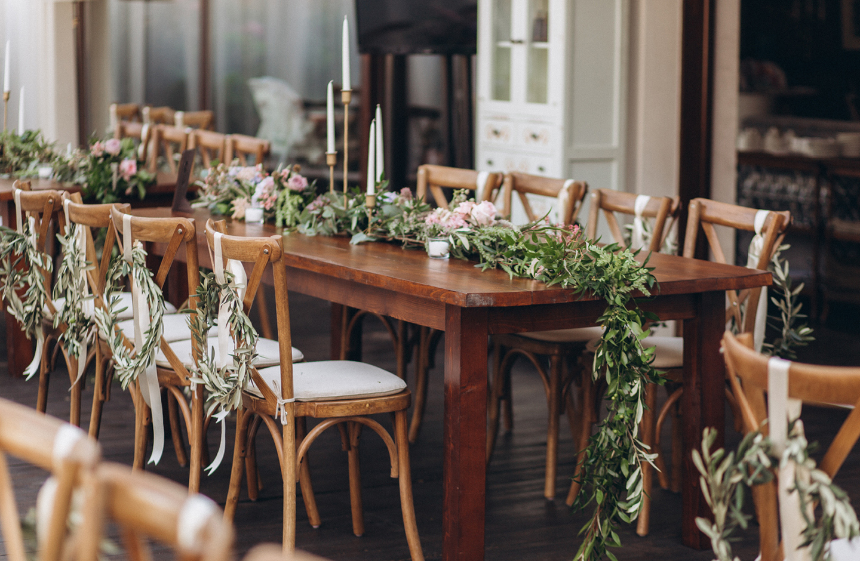 Holztisch ist minimalistisch zur Hochzeit mit grünen Zweigen und rosa Pfingstrosen dekoriert.