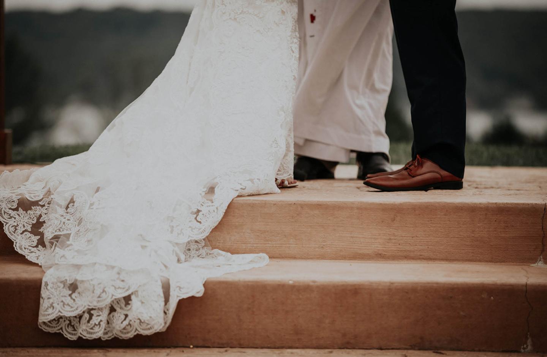 Ein Brautpaar steht sich auf einer Treppenstufe gegenüber. Abgebildet sind nur die Beine des Bräutigams und die lange weiße Schleppe des Brautkleides der Braut.