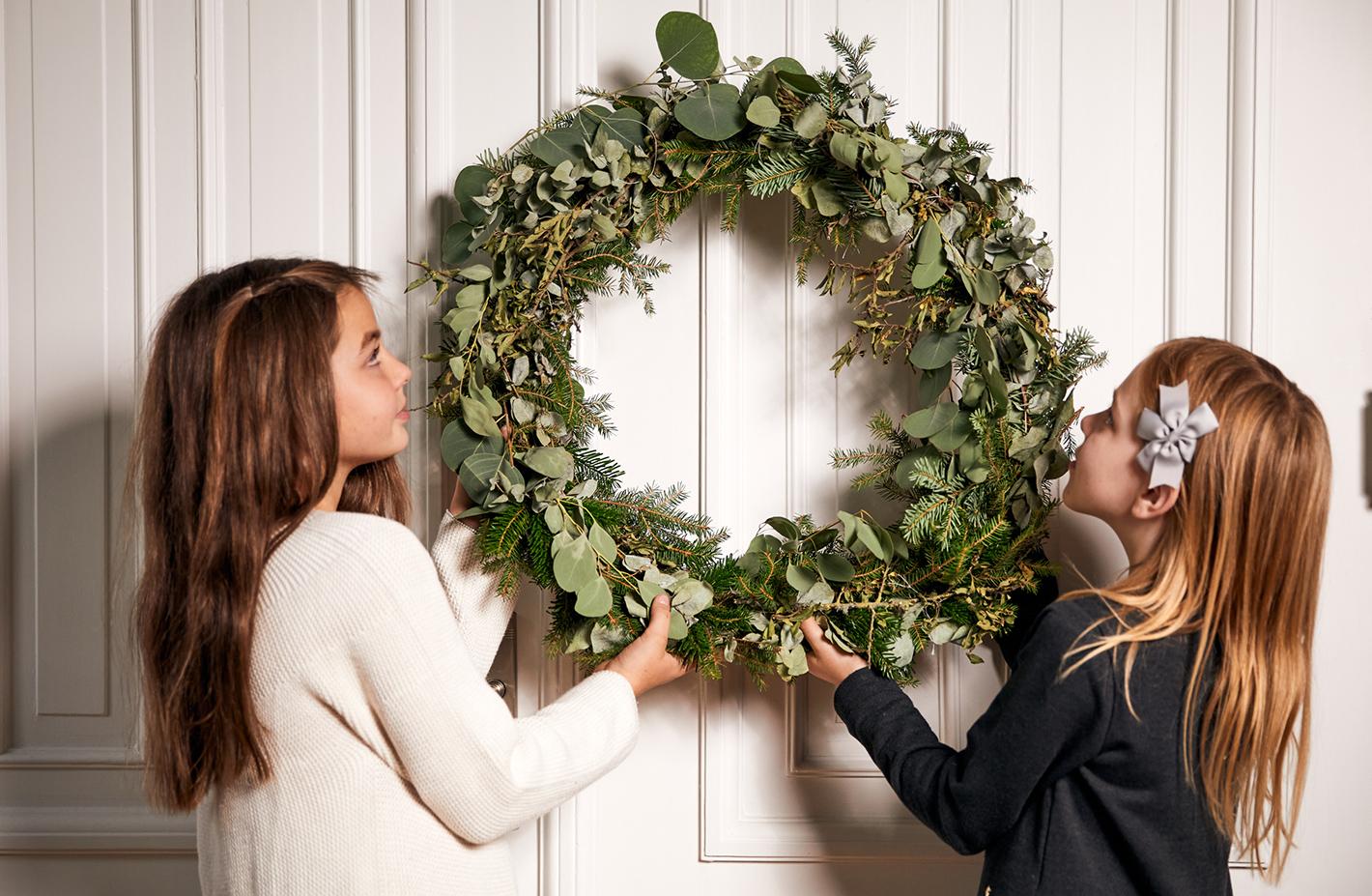 Schwestern hängen gemeinsam den Weihnachtskranz als Dekoration für Weihnachten auf als Aufgabe der Weihnachtscheckliste