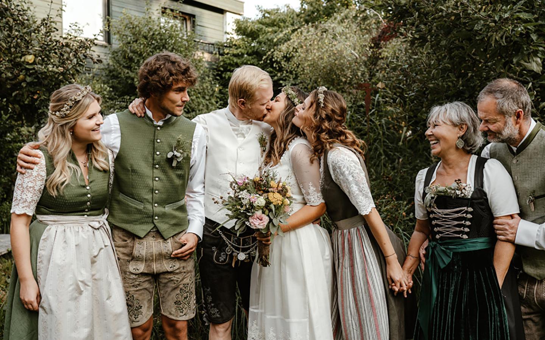 Die Gäste stehen zusammen im Garten, das Hochzeitspaar sich küssend in der Mitte. Alle anderen blicken zu ihnen und strahlen vor Freude über die Hochzeit.