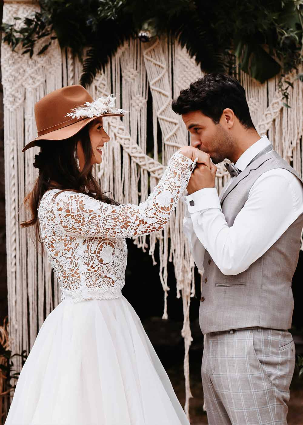 Der Bräutigam küsst sanft die Hand der Braut vor zauberhafter Makramee Deko und Greenery Elementen. Die Braut strahlt in glücklich an und sieht zauberhaft aus in ihrem modernen Hippikleid mit Spitze.