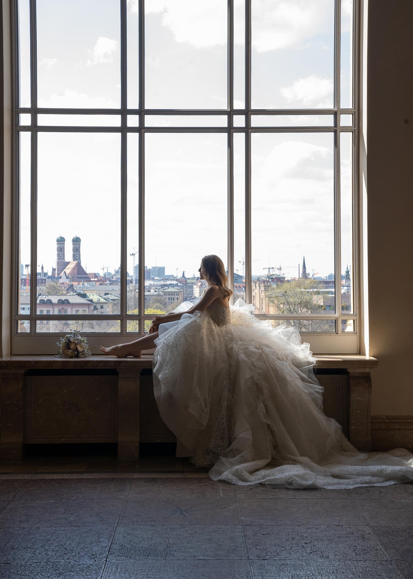 Die Braut sitzt in ihrem pompösen Prinzessinnenkleid passend zum Stil der traditionellen Hochzeitvor einem großen Fenster in der Location und posiert für Fotos.
