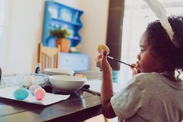 Basteln zu Ostern: Kind malt Ostereier am Esstisch an.