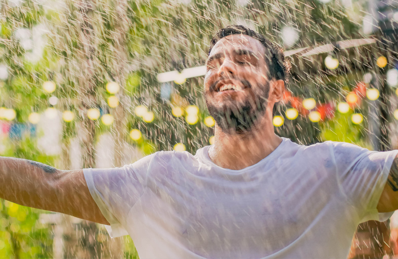 Mann tanzt bei Regen im Garten.