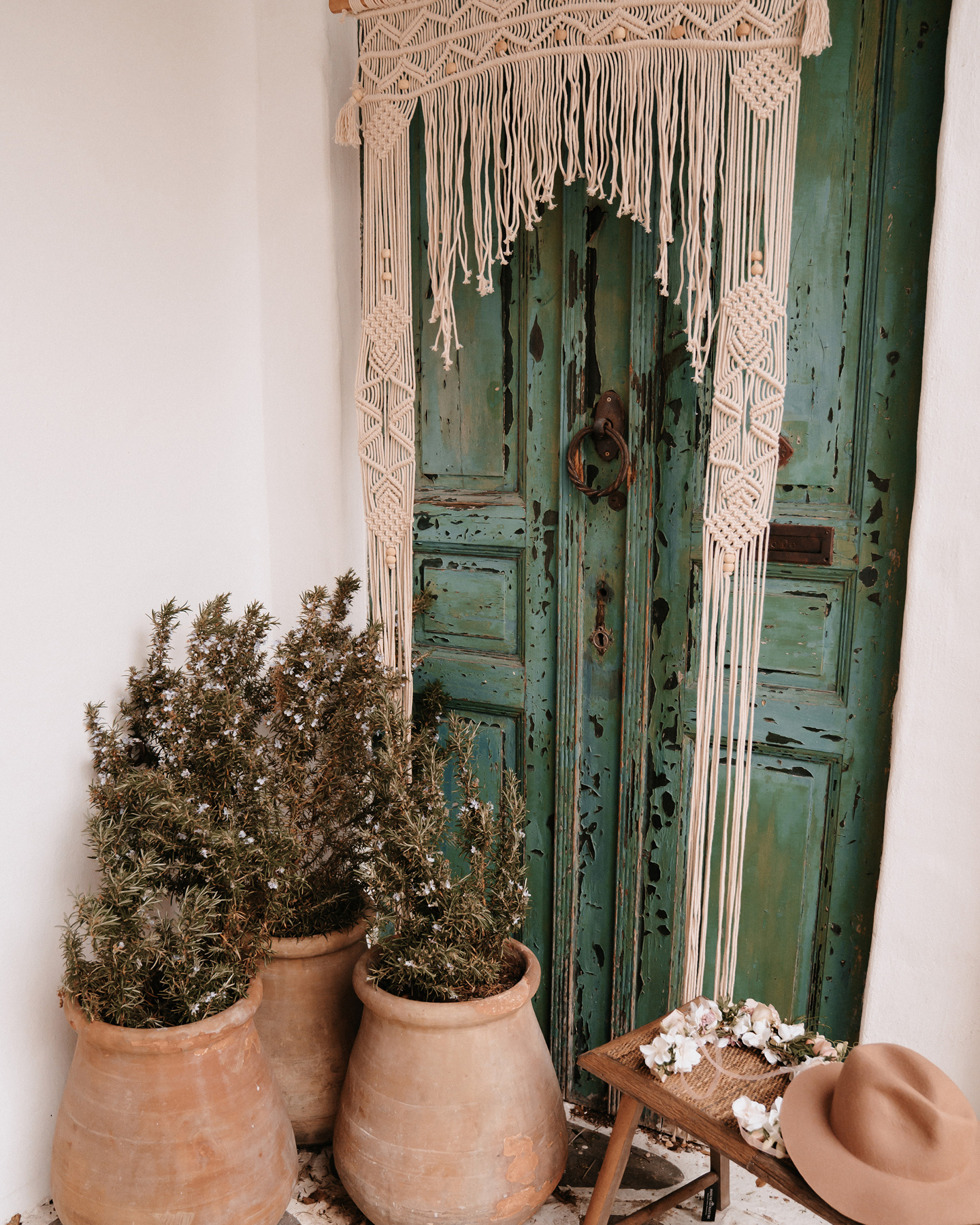 Aufwändig geknotete Makramee Boho Dekoration hängt an grüner Tür.