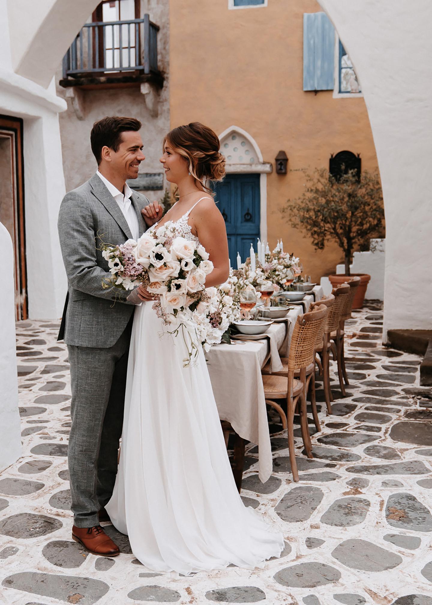 Das glückliche Hochzeitspaar aus Braut und Bräutigam steht vor der Location mit gedecktem Hochzeitstisch und schaut sich verliebt an.