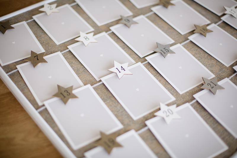 24 Retro Bilder auf Holzbrett mit Sternen-Zahlen befestigt für den perfekten Adventskalender.