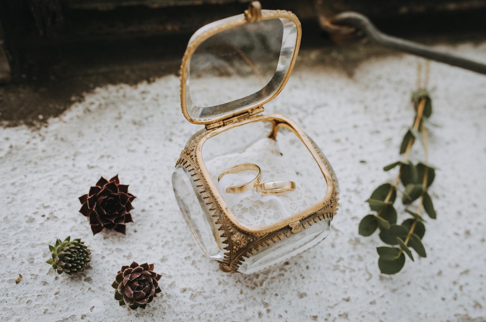 Eheringe in goldener Glasschatulle für minimalistische Hochzeit