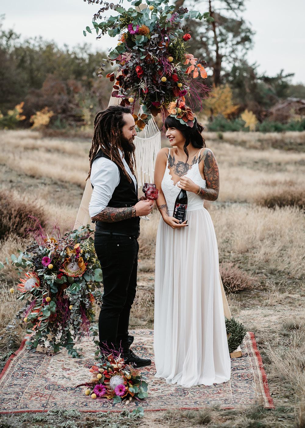 Das Brautpaar steht vor dem mit bunten Blumen geschmückten Traubogen auf der Wiese aus hellen Gräsern in der Hochzeitslocation.