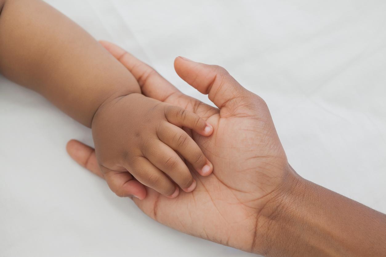 Mutter hält Hand ihres Babys mit spanischem Mädchennamen