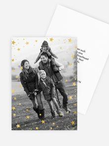 Weihnachtskarte mit funkelnden Sternen in goldener Folie.