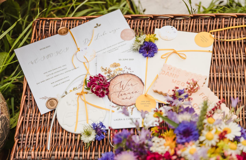 Hochzeitseinladung zur Camper Hochzeit liegt auf einer geflochtenen Holz-Kiste und ist dekoriert mit Wildblumen.