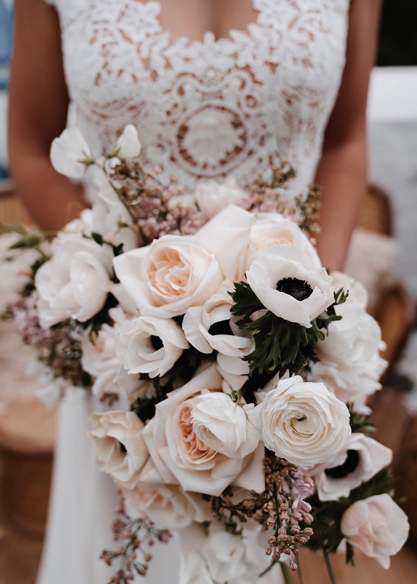 Der Brautstrauß in hellen Orange, Peach, Rosa und Pudertönen wird von der Braut vor ihrem Kleid gehalten.