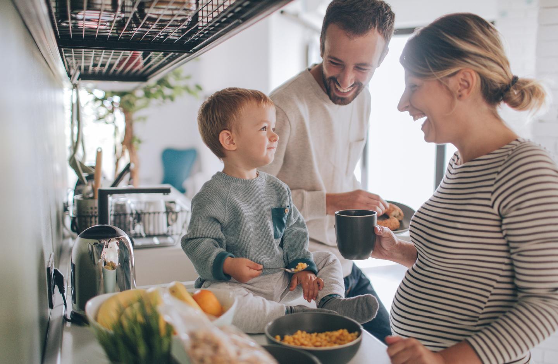 Schwangerschafts Fakten: Schwangere Mama, Papa und Kleinkind essen zusammen Frühstück in der Küche.